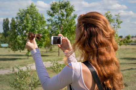 model photographing themselves with smartphone
