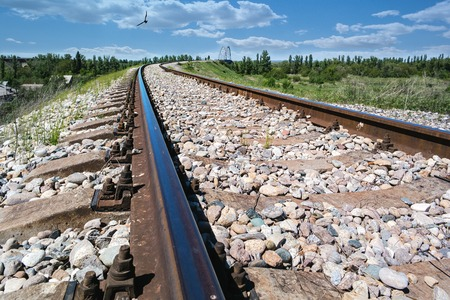 Rails leading to the horizon on a background of blue sky and white clouds