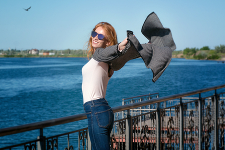 Red-haired girl with glasses on the waterfront 写真素材