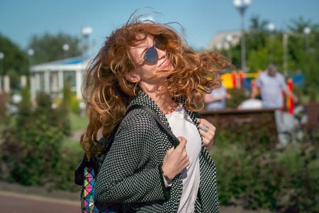 Wind waving red haired girl in sunglasses 写真素材