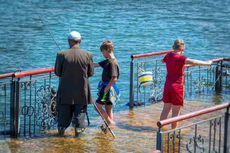 Kids with grandpa fishing on the river Фото со стока