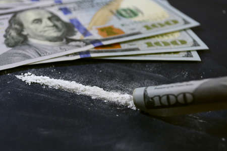 Drugs before use. Cocaine on the table with dollars. Bill tube. Coconut next to dollar bills.