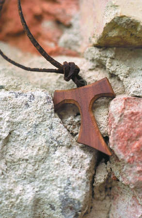 franciscan: Tau, franciscan crucifix on leather strap - background old wall. Stock Photo