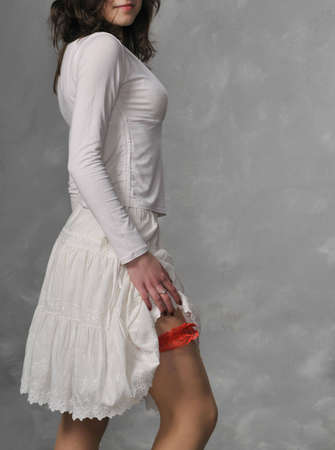 White dressed girl with red garter on the leg gray background Stock Photo - 2518202