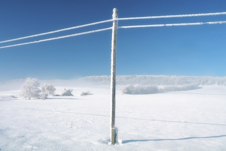 Empty wild winter landscape blue sky, snowy telefony lines photo
