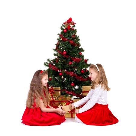 Two little girls sit near Christmas tree, over white background photo