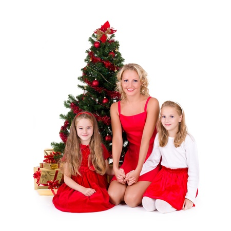 Mother with children sit near Christmas tree, over white background photo