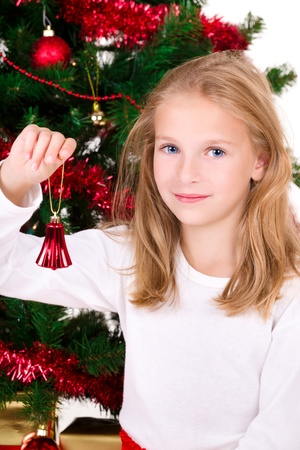 Young girl with bell sit near Christmas tree.   photo