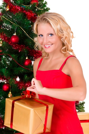 Young beautiful blonde girl with red dress opening Christmas box Stock Photo - 12508312