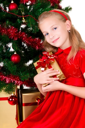 Young girl with gift sit near Christmas tree.  photo