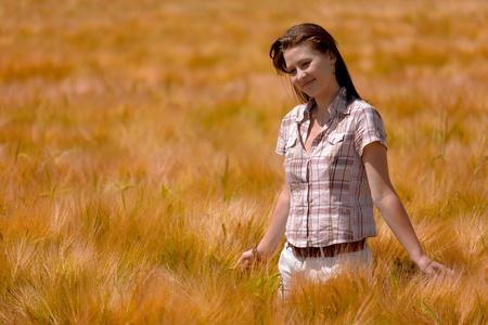 Beautiful girl in the golden wheat field photo