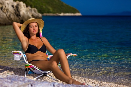 Woman in black bikini and straw hat tans on deckchair in beauty bay photo