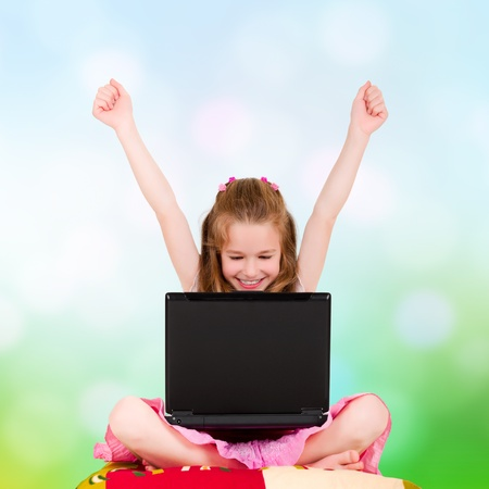 A young girl with a laptop sitting have joyfully hands up photo