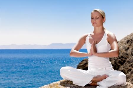 Mooi positief meisje kleding in wit zitten aan de zee op de rots en mediteren in yoga pose