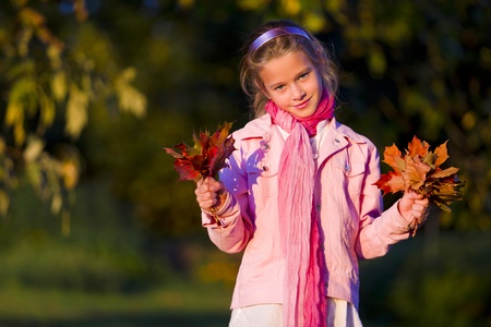 Young girl with leaves in autumn park photo