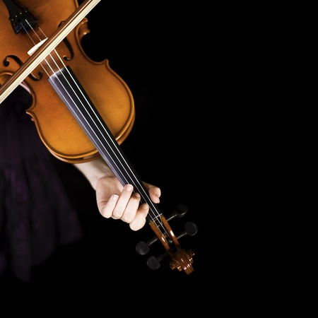 violines: Niña practicando el violín. Sobre fondo negro.