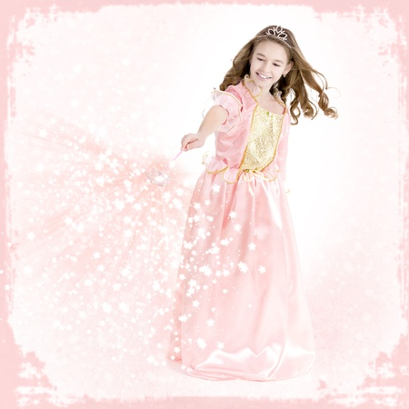 Young girl dressed as a princess with magic wand charms photo