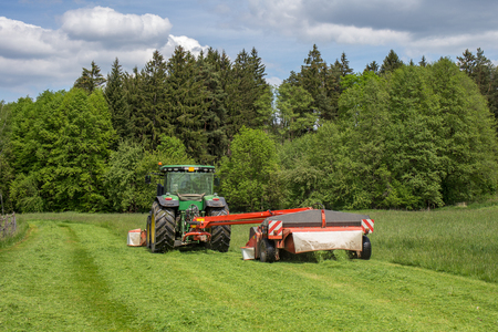 Image of a tractor on meadow. Early grass cutting for BIOGAS production Stock Photo