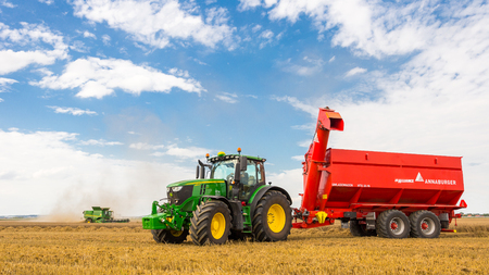Hradec Kralove, Czechia August 4, 2017: Modern John Deere combine harvester model S685i and tractor 6250R at the harvest of wheat near the town Hradec Kralove, Northern Czechia Редакционное