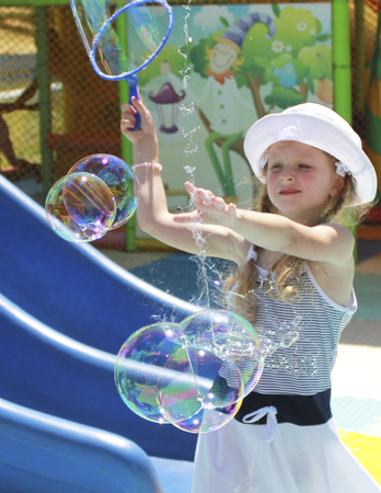 1 person: little girl playing with soap bubbles