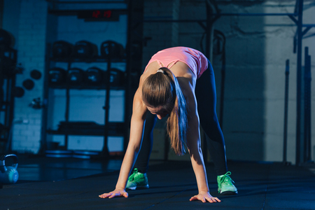 Fit woman in colourful sportswear doing burpees on a exercise mat in a grungy industrial type space