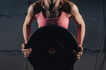Muscular young fitness woman lifting a weight crossfit in the gym. Fitness woman deadlift barbell. The gym on the red wall is written SPORT. Crossfit woman. Crossfit style. Stock Photo