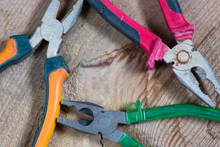 Different tools on a wooden background, pliers