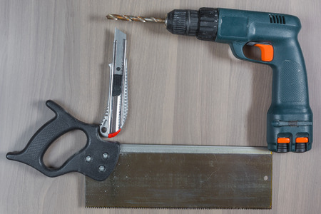 Different tools on a wooden background. Drill, knife, saw