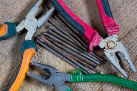 alicate: Different tools on a wooden background. Nails, pliers Foto de archivo