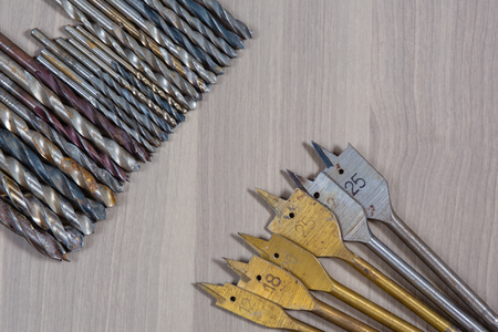 Different tools on a wooden background. drill, Wood drill, concrete drill bit Stock Photo