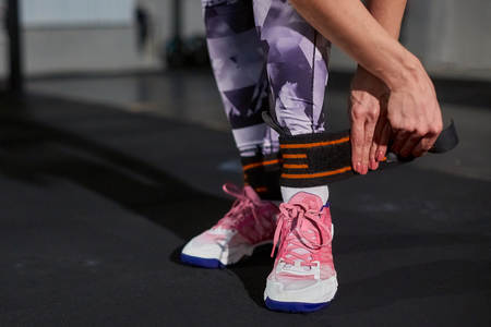 fastens: Beautiful girl in a gym on a background of a concrete wall fastens a leg on an elastic bandage. Cross fit
