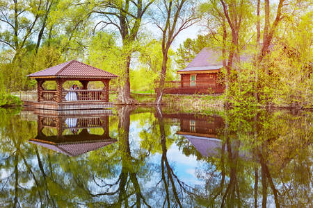 The bride and groom stand in a wooden gazebo on the lake. Spring trees are reflected in the water