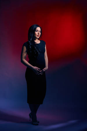 Beautiful pregnant woman with bright make-up, long black hair, in a black-fitting dress posing in a photo studio Stock Photo