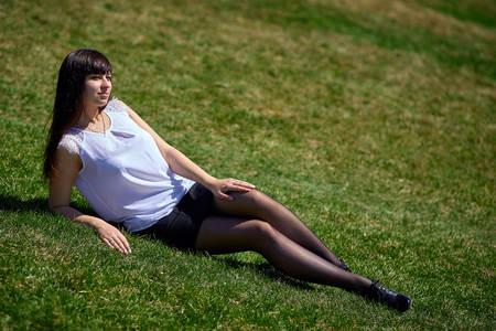 Mooie brunette meisje met lange benen in zwarte panty en korte rok ligt op het gras