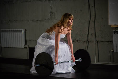 gym dress: Beautiful and muscular bride blonde in a wedding dress doing an exercise with a barbell in a gym, crossfit