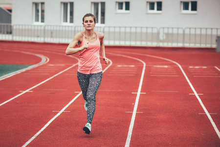 Muscular and beautiful girl doing exercises. Athletics girl, stadium