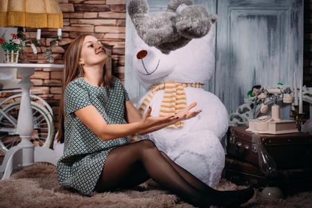 Eine schöne sexy Mädchen in einem kurzen Kleid und Strumpfhosen sitzt auf dem Boden mit einem großen Teddybär in einem Fotostudio