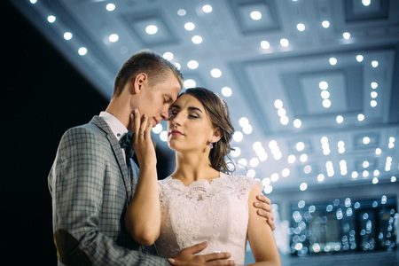 The bride and groom stand on the beautiful porch of the hotel at night Stock Photo