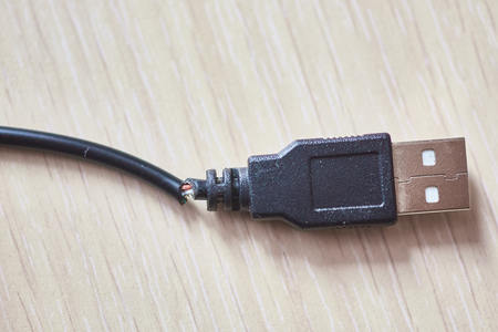 Broken usb cable on a wooden table
