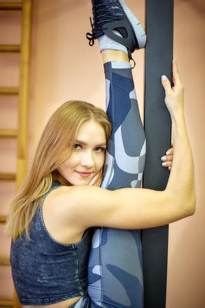 a Fitness, woman training yoga in the gym. Makes stretch stand