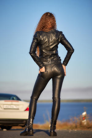 beautiful sexy girl with long hair in a leather jacket and leather pants in sunglasses gets out of the car at sunset Foto de archivo