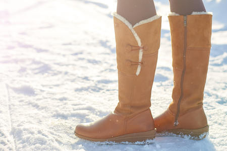 Leg woman winter brown fur boots walking on the snow in a winter park. Closeup outsole of warm boot.