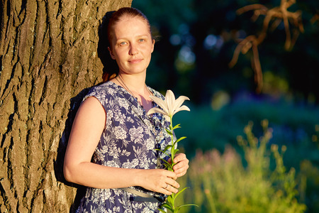 beautiful young caucasian woman is standing in a forest on a summer day at sunset with a lily flower in her hand in a summer dress Stock Photo