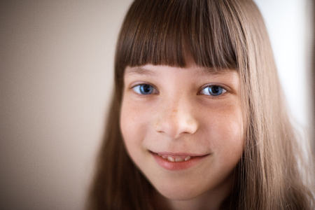 little girl with freckles and blue eyes smiling Stock Photo