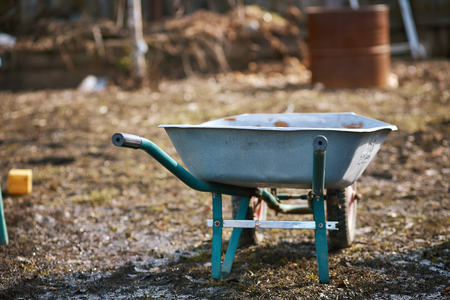 empty garden trolley, wheelbarrow.Old metal trolley on dry grass. Spring in garden. Spring season.cleaning of the garden area, Park. preparation of the garden for planting. Cope space