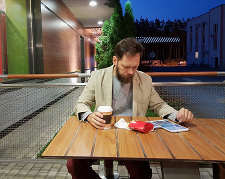 a bearded middle-aged man of Caucasian appearance is sitting at a table in a summer cafe in the evening, watching the news on the screen of a tablet, drinking coffee and eating French fries. Фото со стока