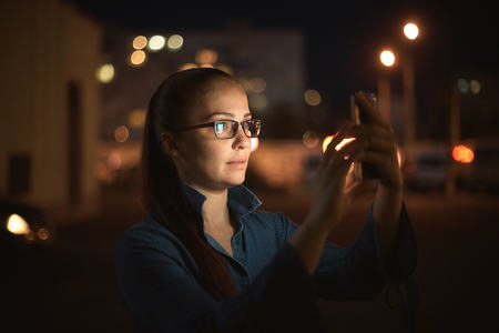 Portrait of young beautiful caucasian woman using smart phone hand hold outdoor in the city night, smiling, face illuminated screenlight - social network, technology, comunication concept