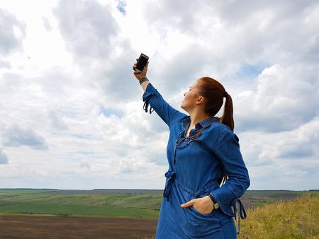 una mujer joven con el pelo rojo y un vestido de mezclilla azul está en las montañas a las afueras de la ciudad y está tratando de captar una conexión celular.