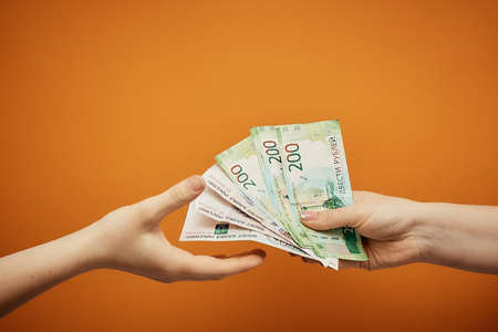 transfer money to each other, two hands and cash on orange background Stock Photo