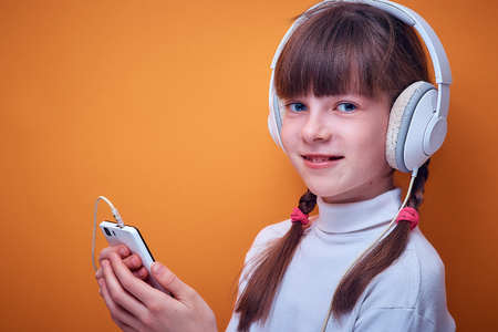 leisure and entertainment , Caucasian teen girl listening to music with headphones using the phone on a colored background, a place for text Imagens